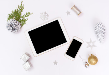 Computer laptop mobile display on table with isolated white screen for mockup in Christmas time. Christmas tree, gifts, decorations in background.