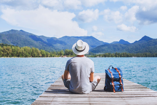 summer travel, young romantic man tourist wanderlust sitting on wooden pier