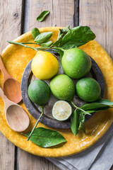 Limes with a lemon on a yellow plate and a wooden table, next to a wooden spoon.