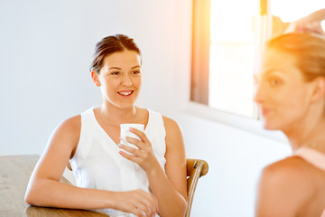 Young woman with her friend having tea at home