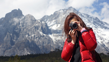 Young girl photographer holding nikon DSLR, she force on other, with snow mountain Jade Dragon background in Lijiang,  in winter, in Yunnan China wide mountain range