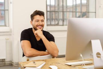 mann schaut zufrieden auf seinen computer
