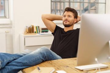 junger unternehmer legt entspannt die füße auf den tisch