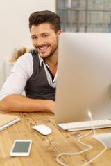 lächelnder mann mit computer und handy im büro