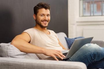 mann sitzt auf dem sofa und surft im internet