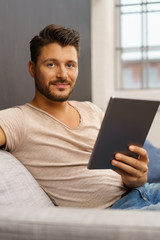 mann sitzt auf dem sofa und hält sein tablet in der hand