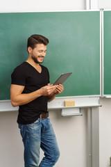 lehrer steht an der tafel und schaut auf sein tablet