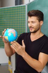 lehrer steht im klassenzimmer und hält einen globus in der hand