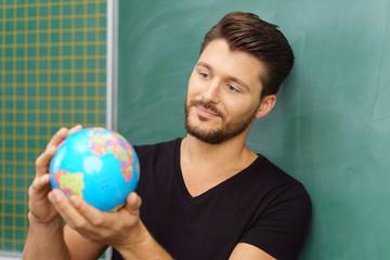 lehrer schaut auf globus