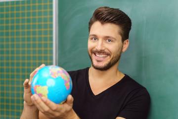 lächelnder lehrer steht vor der tafel und hält einen globus in der hand