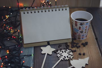 A glass of coffee or cappuccino and coffee beans, wooden sticks: a star, a snowflake and a Christmas tree, an open notebook for notes and glowing New Year's lights on the table