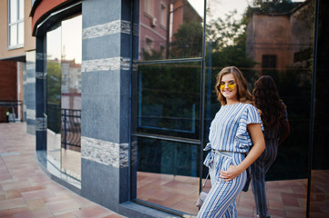 Portrait of a perfect young woman wearing striped overall and yellow sunglasses poses with her handbag on a balcony of a modern building in a town.