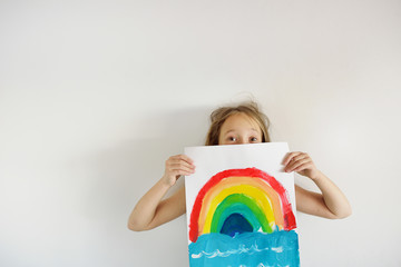 The happy girl with the children's bright drawing of a rainbow in hands on a white background