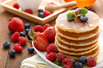 Mixed berry pancake with honey on wooden table
