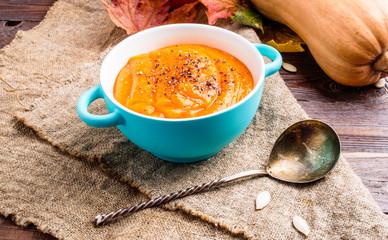 Photo of orange pumpkin soup in saucepan