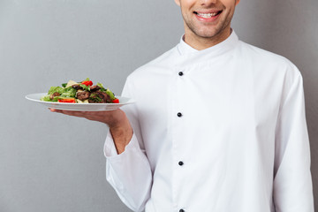 Cropped image of a smiling male chef dressed in uniform