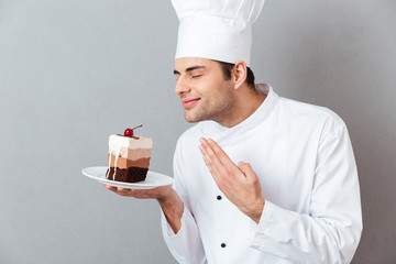 Portrait of a satisfied male chef dressed in uniform