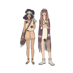 Two young hippie women dressed in stylish clothing decorated with fringe and ethnic ornaments standing together. Beautiful female cartoon characters isolated on white background. Vector illustration.