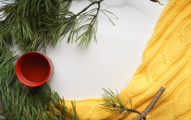Christmas background with a Cup  of tea, branches of pine with large needles and a yellow sweater. Top view close-up