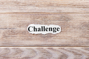 Challenge of the word on paper. concept. Words of Challenge on a wooden background