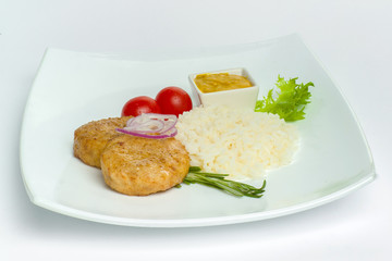 Boiled rice with chicken meatballs , tomato and mustard on a white plate