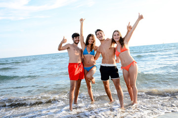 2 young couples friends posing in front of the sea doing the arms in the air making the sign of the success and the happiness.