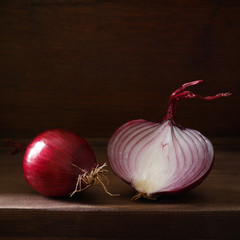 Still life with red onion on a dark background. Red onion in a cut on a wooden board in a low key. Beautiful side soft light. Vegetables, the concept of healthy eating.