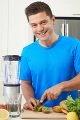 Male Athlete Making Juice Or Smoothie In Kitchen