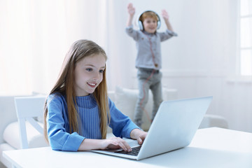 Different activities. Active energetic boy jumping while his sister working on a laptop