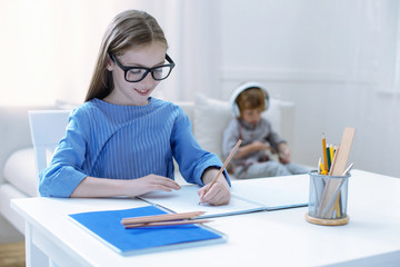 Smart child. Attentive diligent cheerful girl doing homework while her little brother listening to music