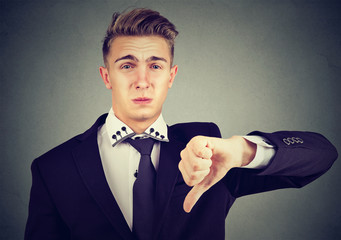 Angry disappointed young business man showing thumbs down sign, in disapproval isolated on gray background. Negative emotion facial expression feelings