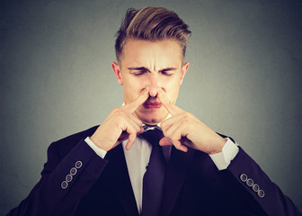 man pinches nose with fingers looks with disgust something stinks bad smell isolated on gray background.