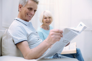 Funny article. Pleasant positive senior man laughing while sitting with his nice old wife and reading a newspaper