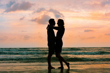 Two silhouettes of romantic couple standing on sunset sea beach of Thailand. Love, romance and relationship concept.