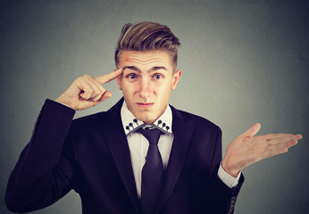 Portrait of angry mad young man gesturing with finger asking are you crazy? Isolated on gray background. Negative emotions feeling body language