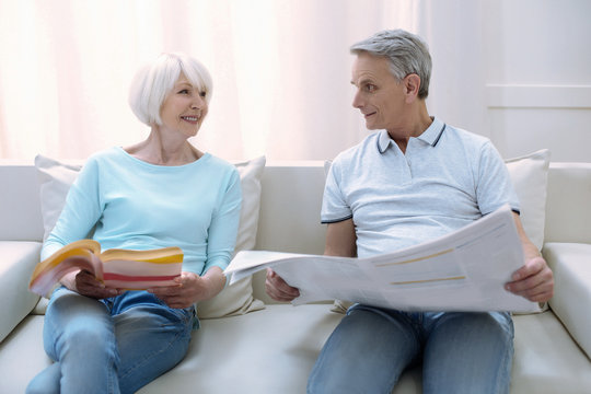 Nice readers. Cheerful friendly old people sitting on a comfortable sofa together and reading