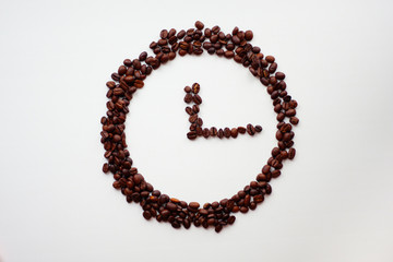 Coffee time concept. Clocks made from grains of coffee on white surface