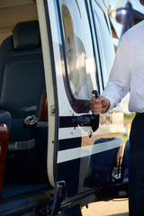 Close Up Of Pilot Opening Helicopter Cabin Door