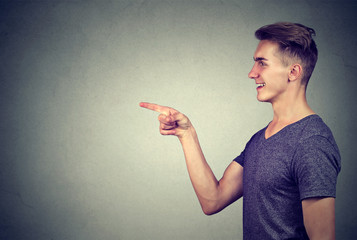 Side profile of a laughing young man pointing finger