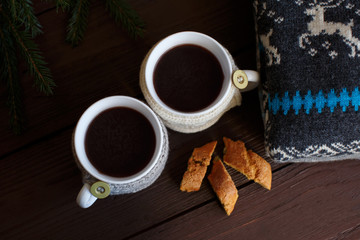 Winter morning, cups of coffee with knitted cup holders near knitted sweater and cake. Ideal for winter couple in love