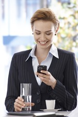 Happy businesswoman reading text message