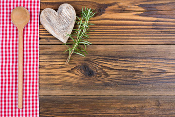 Ein Holzlöffel, Rosmarinzweige und ein Herz aus Holz liegen auf einem rot weiß kariertem Stofftuch auf auf einem rustikalen Holz Hintergund mit Textfreiraum zum selber gestalten