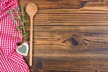Ein alter Holzlöffel, Dekoherz und Rosmarinzweige und ein rot weiß kariertes Stofftuch liegen auf einem rustikalen Holz Hintergund mit Textfreiraum zum selber gestalten