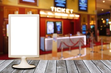 mini blank advertising billboard with blurred image of ticket sales counter at movie theater, copy space for text or media content, advertisement, commercial and marketing concept