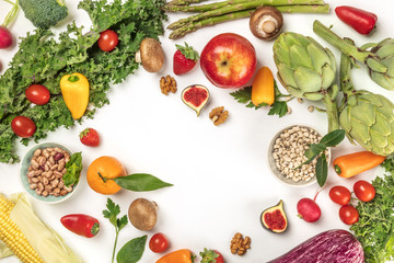 Vibrant fresh vegetables, fruits, and legumes on white