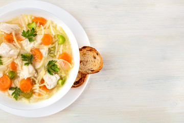 Chicken soup with noodles, overhead photo with copyspace