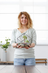 Picture of blonde florist with florarium with stones and succulents
