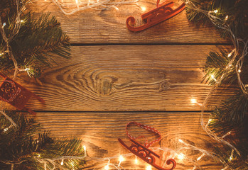 Image on top of wooden table with burning garland, spruce branches, Christmas toys.