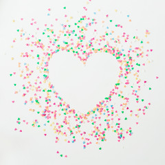 Heart love symbol made of colorful bright confetti on white background. Flat lay, top view copy space.