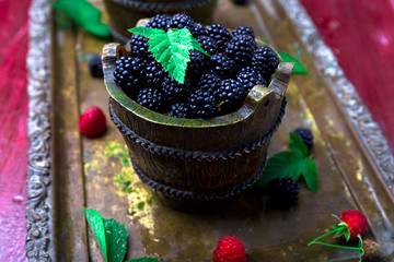 Blackberry with leaf in a basket on vintage metal tray. Top view.  Close up.